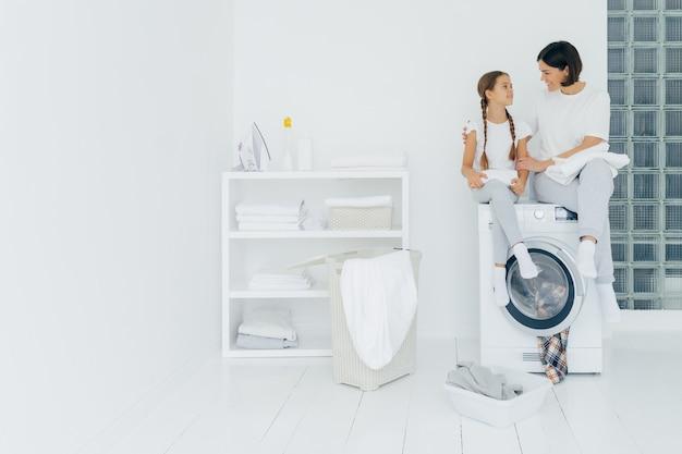 Mulher carinhosa feliz abraça sua filha pequena, sente-se na máquina de lavar