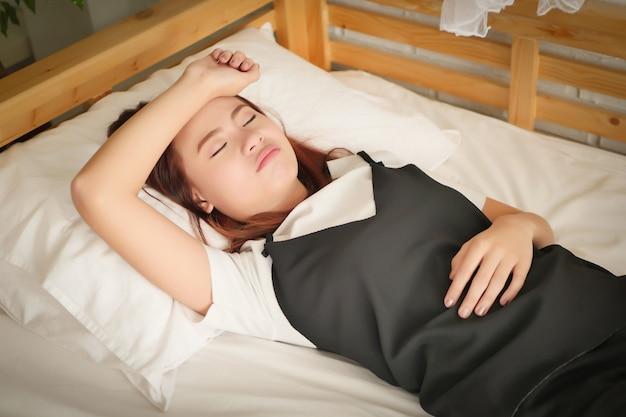 Mulher carrancuda, doente, exausta e inquieta, dormindo com a mão na testa, conceito de doença, dor de cabeça, ressaca, estresse