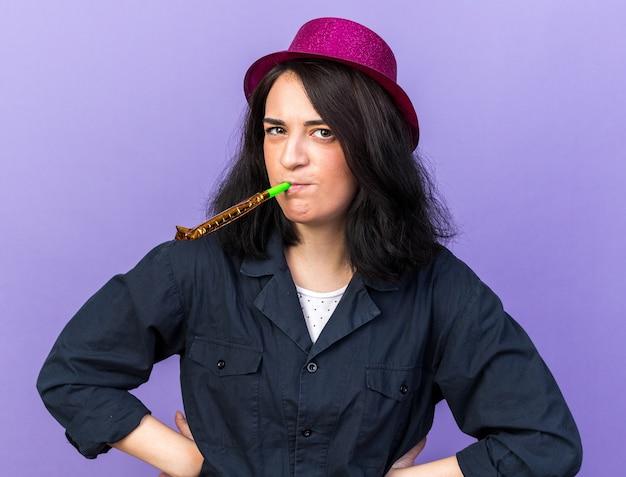 Mulher carrancuda jovem caucasiana de festa usando chapéu de festa, olhando para frente, soprando soprador de festa, mantendo as mãos na cintura, olhando para frente, isolada na parede roxa