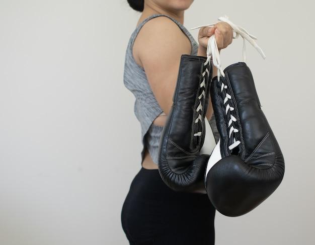 Mulher carrega luvas de boxe pretas para fazer exercício