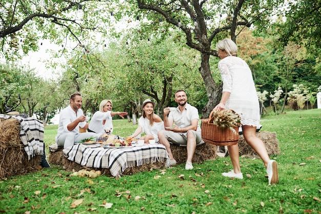 Mulher carrega uma cesta de trigo seco. grupo de amigos adultos descansam e conversam no quintal do restaurante na hora do jantar.