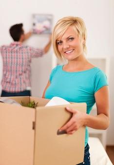 Mulher carregando caixa com itens para um novo apartamento