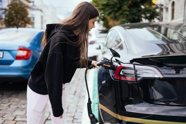 Mulher carregando carro elétrico na estação de carregamento.