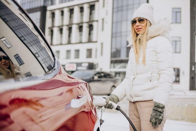Mulher carregando carro elétrico vermelho, no inverno