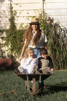 Mulher carregando filhos com carrinho de mão