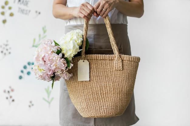 Mulher carregando hortênsias em uma bolsa de vime
