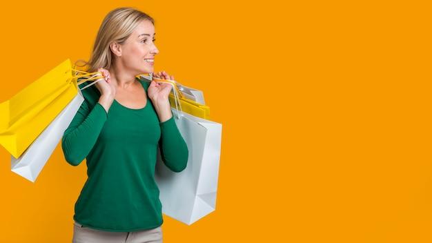Mulher carregando muitas sacolas de compras após uma maratona de compras