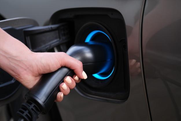 Mulher carregando o carro usando o plugue elétrico closeup