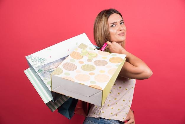 Mulher carregando sacolas de compras com expressão neutra.