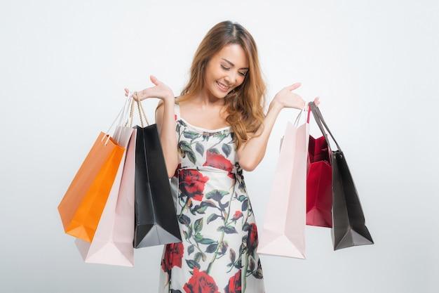 Mulher carregando sacolas de compras em cinza isolado