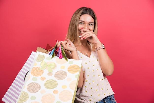 Mulher carregando sacolas de compras enquanto ri na parede vermelha.