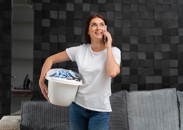 Mulher carregando um monte de roupas sujas na cesta