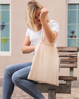 Mulher carregando uma sacola de compras e procurando nela