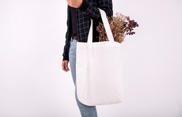 Mulher carregando uma sacola simulada acima com flor.