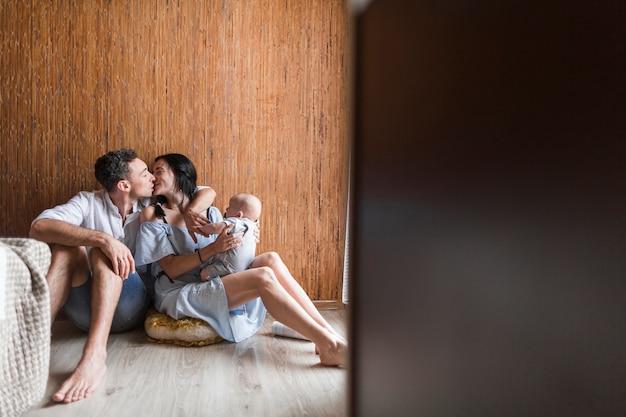 Mulher, carregar, bebê, beijando, dela, marido, sentar chão