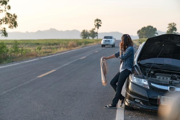 Mulher carro quebrado pedindo ajuda.