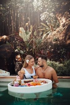 Mulher casada e homem com mesa flutuante, há muitos alimentos tropicais diferentes, nadar na piscina e desfrutar de suas férias.