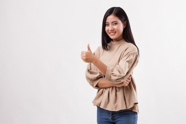 Mulher casual apontando o polegar para o espaço em branco, estúdio do modelo da mulher árabe asiática