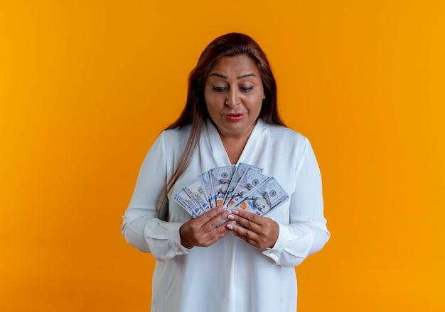 Mulher casual caucasiana de meia-idade impressionada segurando e olhando para o dinheiro