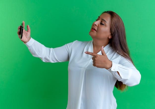 Mulher casual caucasiana de meia-idade tirando uma selfie e mostrando o gesto