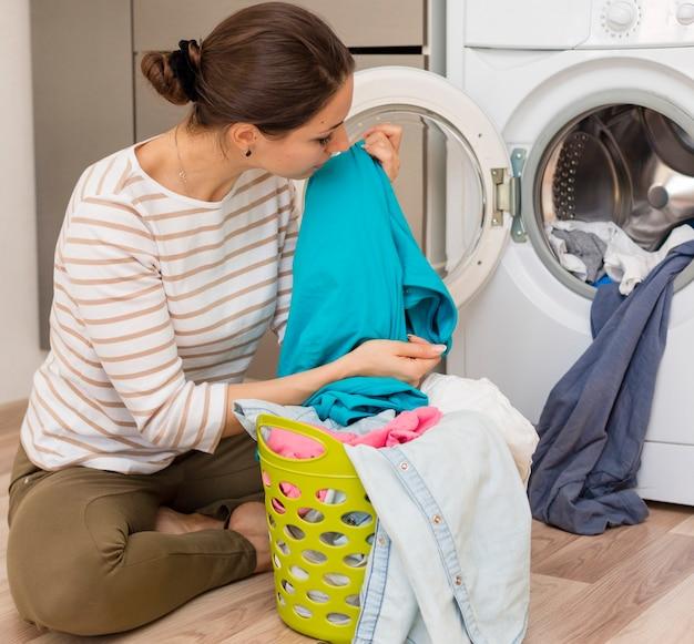 Mulher casual, cheirando a roupa limpa