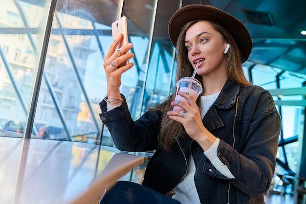 Mulher casual elegante hipster atraente na moda no chapéu com fones de ouvido sem fio e telefone celular bebe milk-shake doce durante o relaxamento no café. pessoas modernas com estilo de vida digital