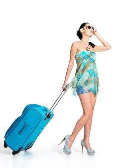 Mulher casual em pé com uma mala de viagem
