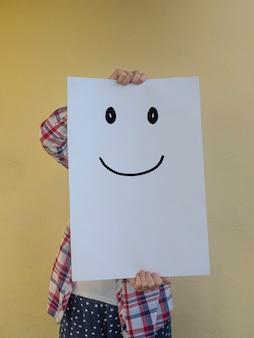 Mulher casual escondendo o rosto atrás de um outdoor em branco com um rosto sorridente.