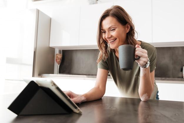 Mulher casual feliz tomando café e usando computador tablet na cozinha