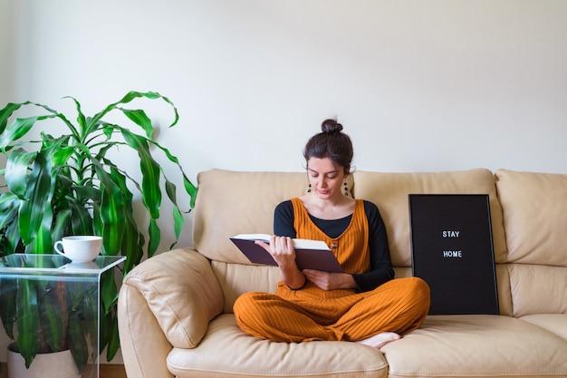 Mulher casual, sentar no sofá na casa dela. ficar em casa conceito. coronavírus da doença do vírus pandêmico coberto 19.