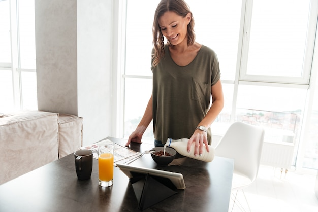Mulher casual sorridente comendo junto à mesa na cozinha e olhando para o computador tablet