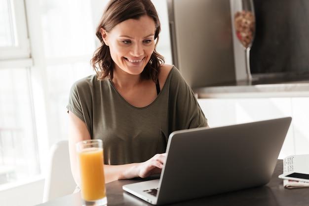Mulher casual sorridente usando computador tablet pela mesa na cozinha
