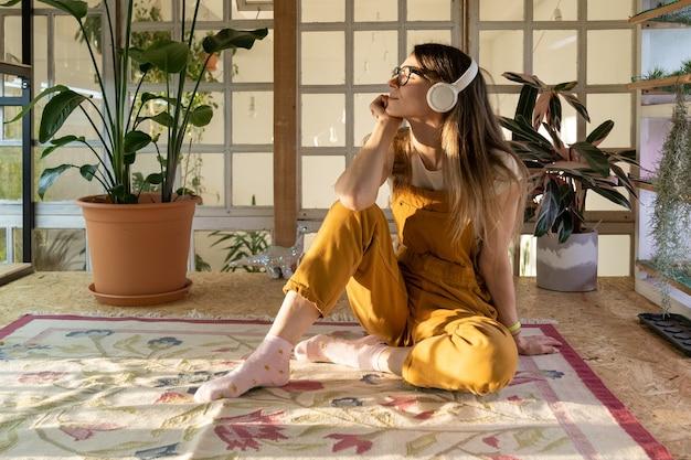 Mulher casual usando fones de ouvido e ouvindo música relaxada em casa sentada no tapete