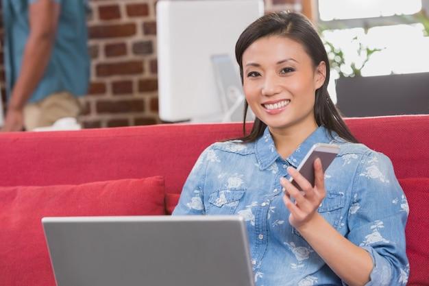 Mulher casual usando laptop e celular no sofá