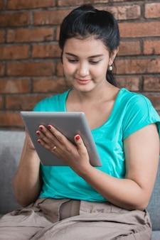 Mulher casual usando tablet em casa