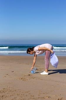 Mulher catando lixo e plásticos, limpando a praia