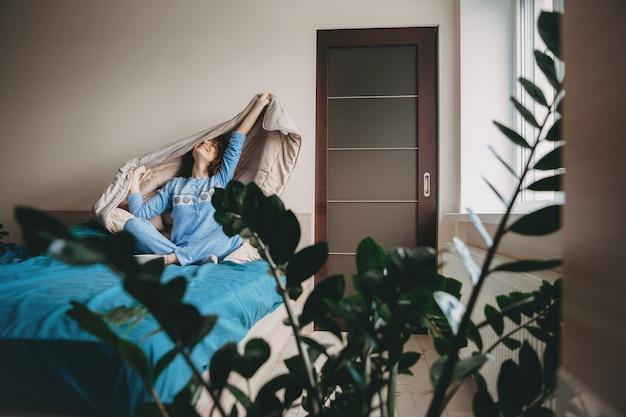Mulher caucasiana acordando da cama vestida com um pijama azul, sorrindo e se espreguiçando com sua colcha