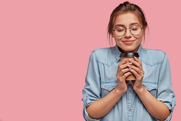 Mulher caucasiana adorável e satisfeita segurando uma bebida aromática, tomando cappuccino ou café, sentindo calor, fechando os olhos de prazer