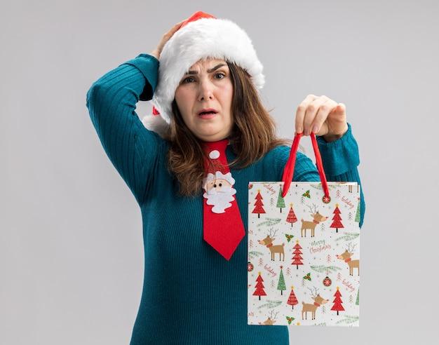 Mulher caucasiana adulta ansiosa com chapéu de papai noel e gravata de papai noel coloca a mão na cabeça e segura uma caixa de presente de papel isolada na parede branca com espaço de cópia