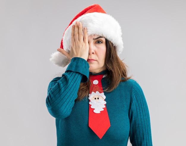 Mulher caucasiana adulta confiante com chapéu de papai noel e gravata de papai noel cobrindo os olhos com a mão isolada na parede branca com espaço de cópia