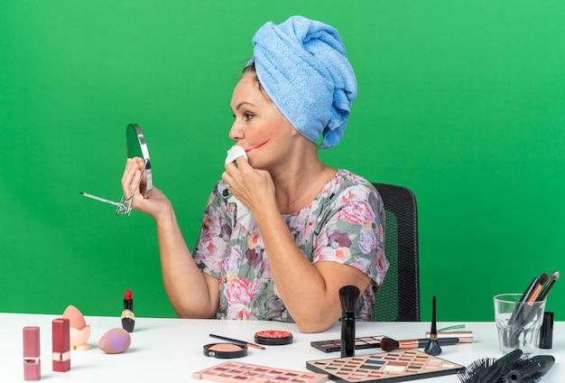Mulher caucasiana adulta confiante com o cabelo enrolado em uma toalha, sentada à mesa com ferramentas de maquiagem, limpa a boca com um guardanapo molhado isolado na parede verde com espaço de cópia