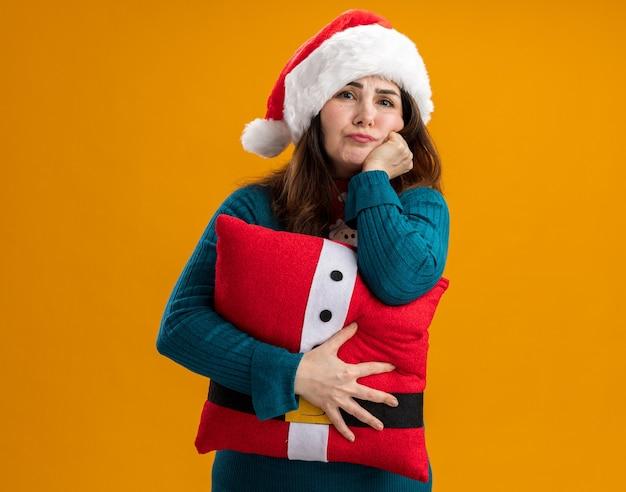 Mulher caucasiana adulta decepcionada com chapéu de papai noel e gravata de papai noel coloca a mão no queixo e segura o travesseiro decorado isolado na parede laranja com espaço de cópia