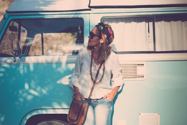 Mulher caucasiana adulta elegante e bonita, levanta-se com van vintage azul - conceito de estilo de vida de motorista de viagens e moda - pessoas alternativas com veículo
