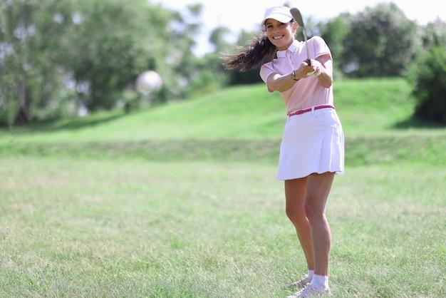 Mulher caucasiana adulta sorridente no clube de golfe, batendo no retrato de bola.