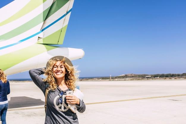 Mulher caucasiana alegre com cabelo encaracolado e um chapéu na frente do avião com o celular e o livro pronto para a viagem de férias de viagem. passageira empolgada no aeródromo em frente ao avião