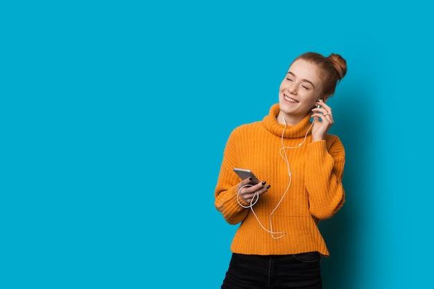 Mulher caucasiana alegre com sardas e cabelo vermelho está ouvindo música usando fones de ouvido e celular em uma parede azul com espaço em branco