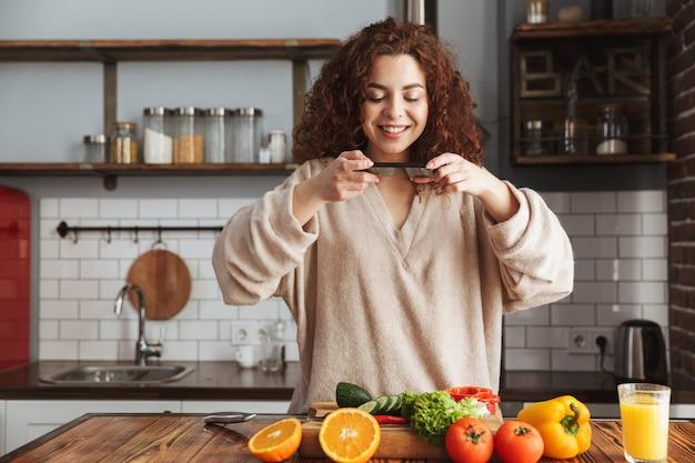 Mulher caucasiana alegre pegando comida no smartphone enquanto cozinha salada de legumes frescos no interior da cozinha em casa