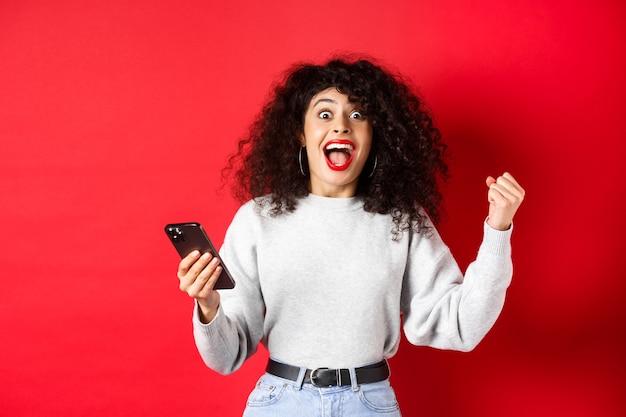Mulher caucasiana animada com cabelos cacheados, cantando, ganhando prêmio online, segurando o smartphone e triunfando, em pé na parede vermelha.