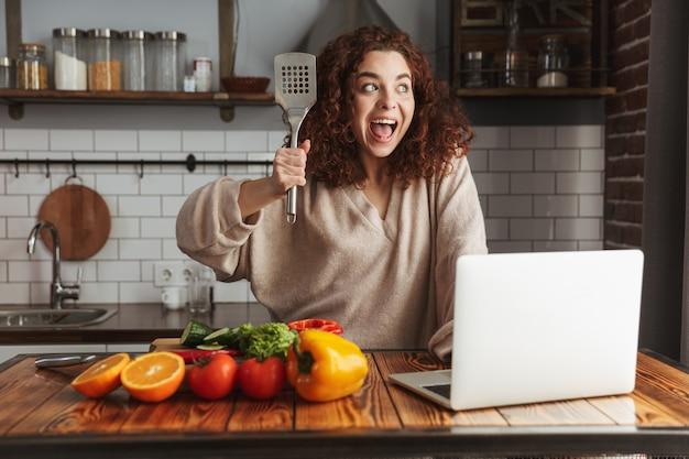 Mulher caucasiana animada usando laptop enquanto cozinha salada de legumes fresca no interior da cozinha em casa