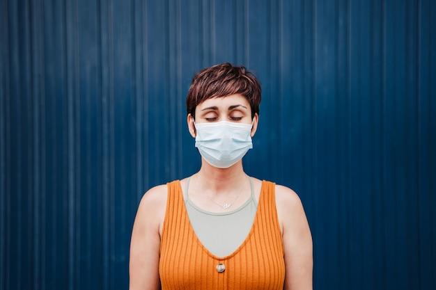 Mulher caucasiana ao ar livre com os olhos fechados, usando máscara facial. pandemia durante o conceito de distância social do vírus corona.